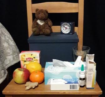 stoel naast een bed. op de stoel staan allerlei zaken die handig kunnen zijn bij griep