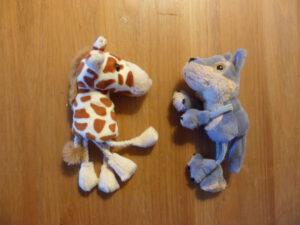 Twee vingerpopjes, een giraffe en een jakhals, liggen op tafel en kijken elkaar aan.