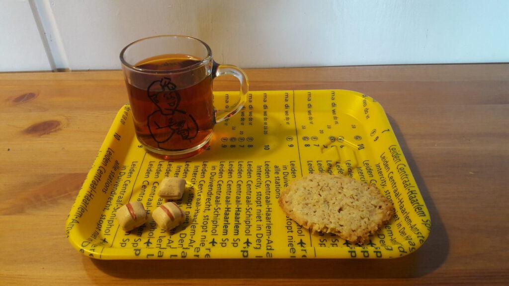 dienblaadje met koekje, snoepjes en een beker thee. op de beker staat een tekening van het gebaar 'thee'.