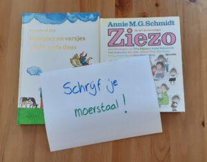 twee kinderboeken met een blad papier waar met de hand  'Schrijf je moerstaal!' op geschreven staat