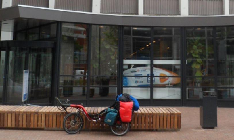 Mijn ligfiets met vakantiebagage voor de ingang van de Faculteit Bewegingswetenschappen. Achter het glas is de gestroomlijnde  wereldrecord fiets zichtbaar. Door de  ligfiets, een aanpassing aan mijn beperkingen, kan ik mijn mogelijkheden gebruiken voor een fietsvakantie.